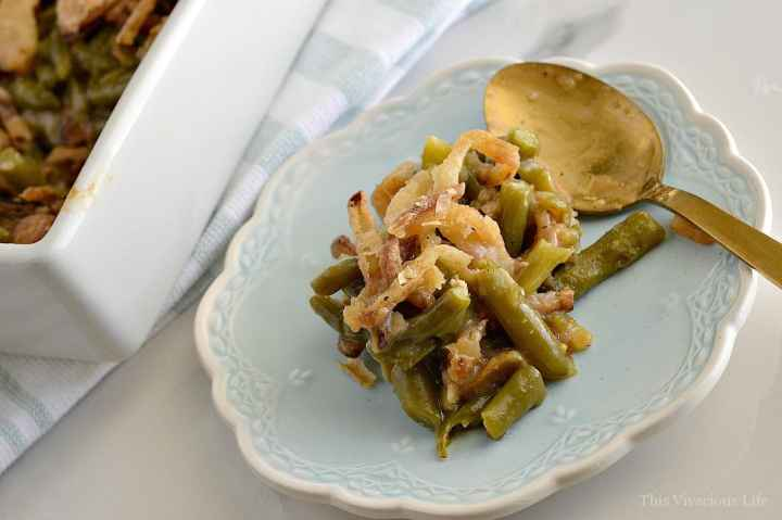 Gluten-free green bean casserole on a blue plate with gold spoon