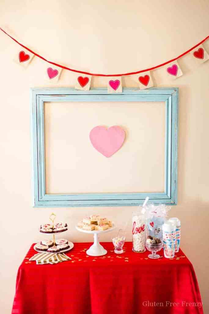 """Galentines Day Favorite Things Party as featured on Hostess with the Mostess! Have you been wanting to create the perfect girls night in for Galentines Day? This party is so fun and easy to put together. From the sweets and cocoa bar, including ooey gooey red velvet cookies (recipe included), to a fries before guys bar, this party has it all. There is even a kiss """"kard"""" making station for writing up something kind for your cutie. Each girl brings a few of their favorite things and everybody goes home with the same amount they brought. So fun! There is even a philanthropy aspect with blessing bags they made for the local homeless shelter. Get all the details and photos for this epic DIY party on glutenfreefrenzy.com."""
