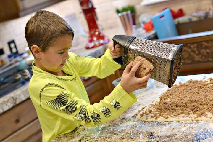 Frozen brown sugar butter cinnamon roll filling being grated by a little boy onto the dough.