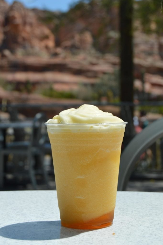 Cup of Disneyland Reds Apple Freeze with mountains in the back