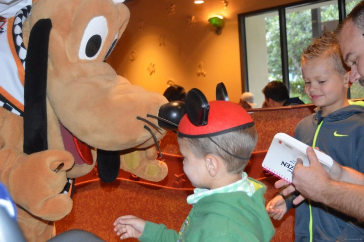 Two kids meeting Goofy at Disneyland