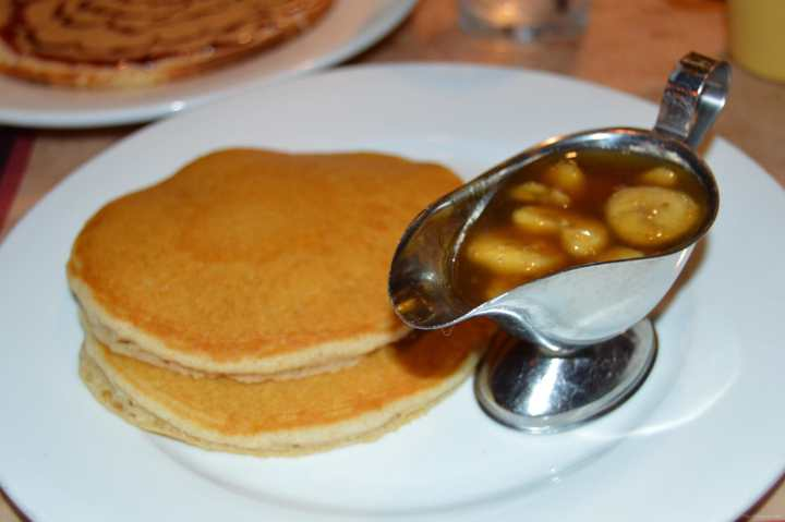 Two gluten-free pancakes and bananas foster on a white plate