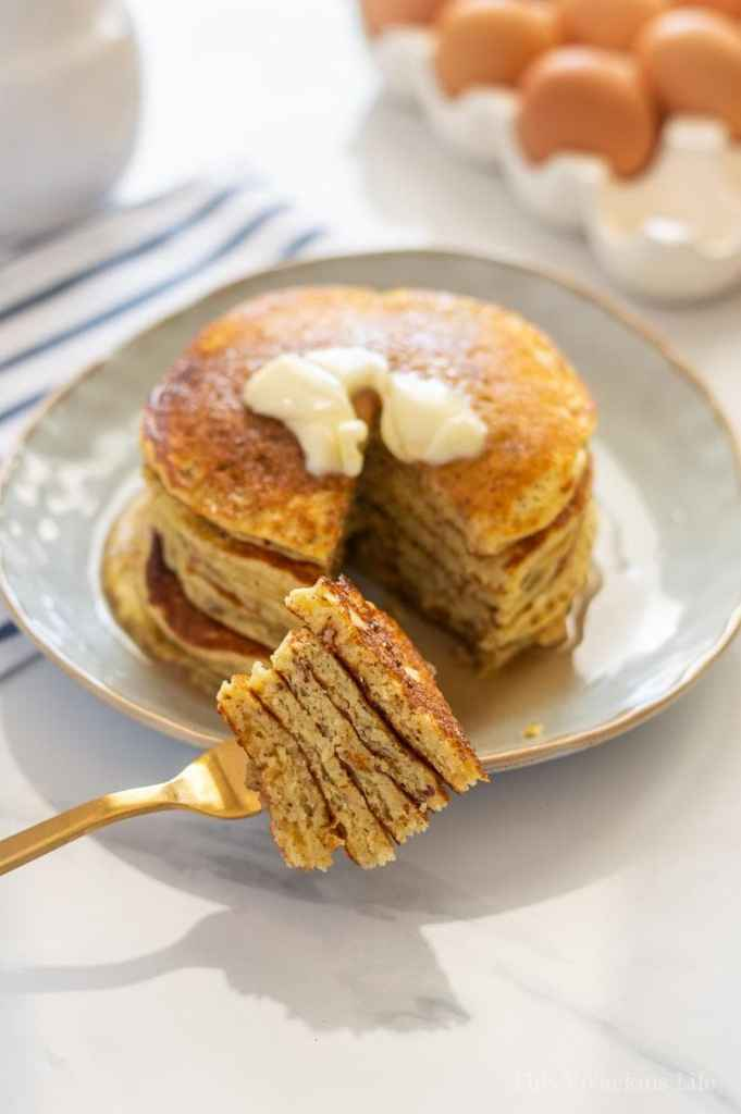 Short stack of pancakes with butter and a bite on a fork