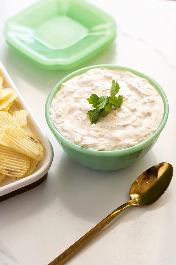 A bowl of Sour Cream Dip with Chives on Top next to Potato Chips and a Spoon