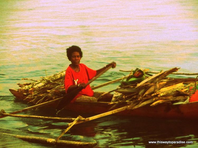 Man on a wood-filled longboat, Raja Ampat