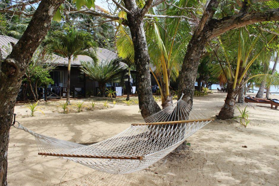 A hammock over white sand beach, Tonga