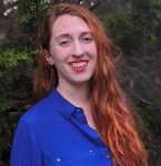 A young caucasian woman with vibrant red hair in a bright blue button up, smiling in front of greenery.