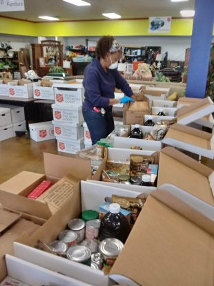 Volunteer boxing canned goods in the food distribution warehouse.
