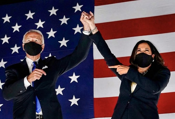 President-Elect Joe Biden and Vice President-Elect Kamala Harris holding hands in the air in front of an American flag during their winning speech.