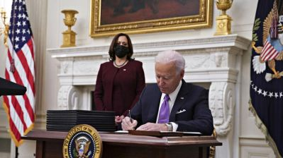 Biden signing executive orders while Harris stands in the background in a maroon outfit wearing a black mask.