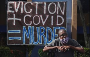 """Man of color with a mask on sitting in front of a sign that says """"eviction + covid = murder"""""""