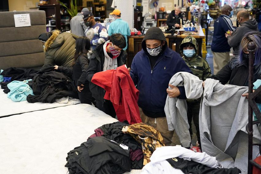 People in masks and sweaters sorting through clothing donations