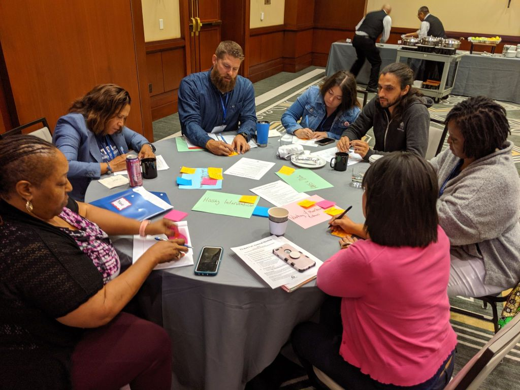 A group of conference participants working at a table during the 2019 annual conference.