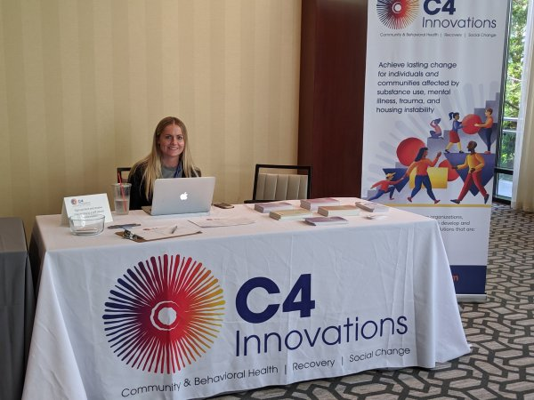 Woman sitting behind a table for c4 innovations.