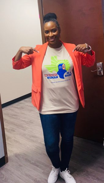 Advocate standing pointing her fingers at her homelessness awareness day shirt that is under a bright tangerine colored jacket