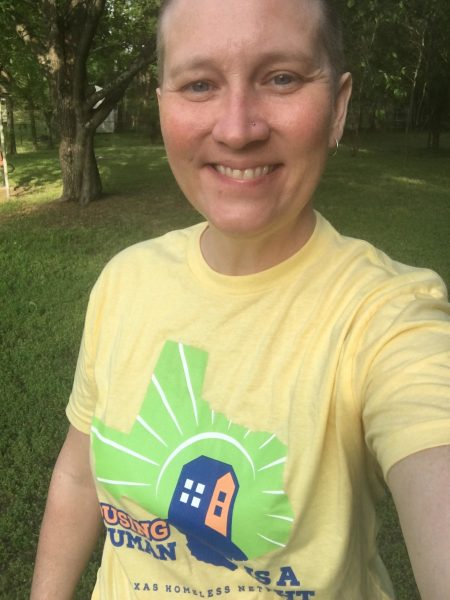 Jaynna smiling outside with greenery behind them in a yellow homelessness awareness day tshirt.