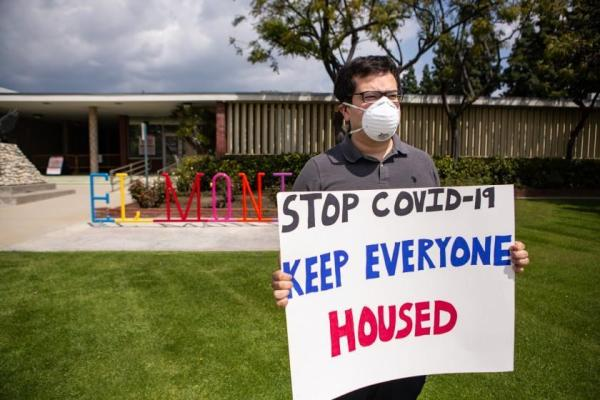 """Person in front of a building with a mask on holding a sign that says """"Stop COVID-19. Keep everyone housed."""""""