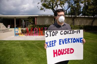 Person in front of a building with a mask on holding a sign that says