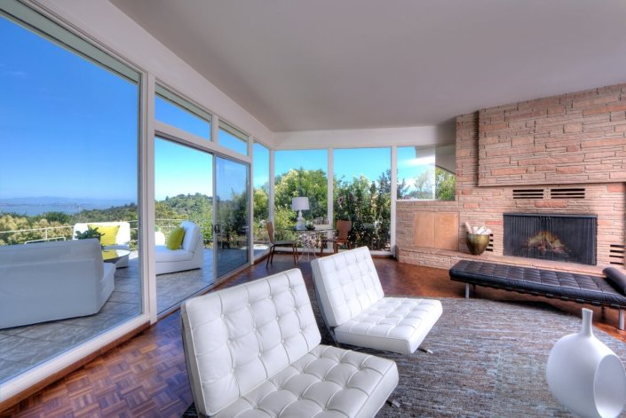 Living room with glass wall to left and view of bay