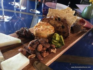 photo of the appetizer board with pickles and nuts and breads