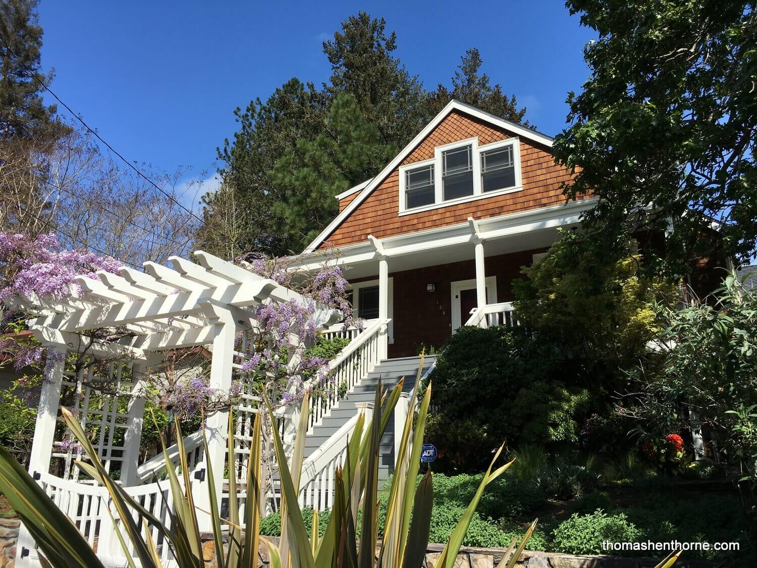shingled home with wisteria in bloom