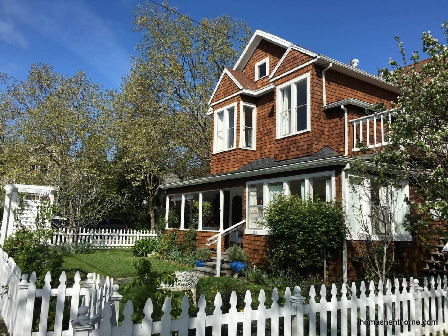 photo of home with shingles white trim and white picket fence