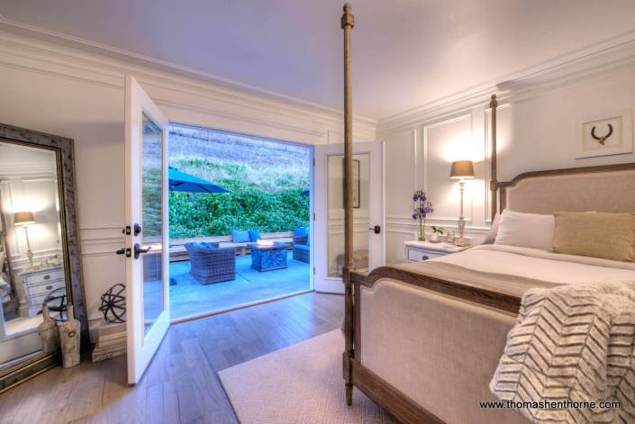 Master bedroom with two French doors open to back patio
