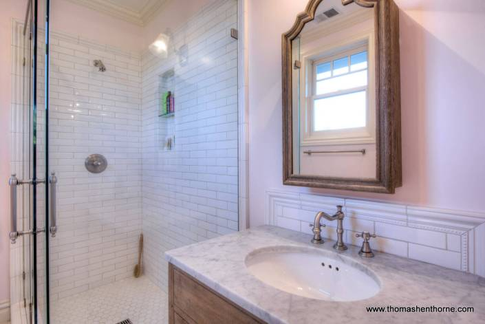 bathroom with vanity with marble counter and shower with subway tile