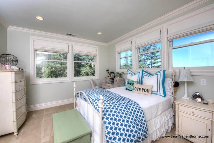 corner bedroom with blue and white bedspread