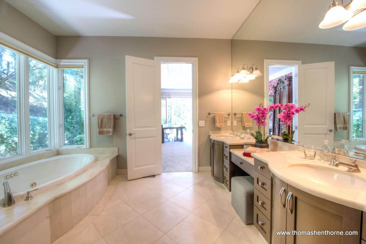Master bathroom with tub and dual vanities