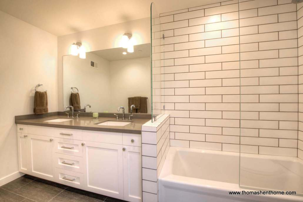 downstairs bathroom with dual vanities and shower / tub combination