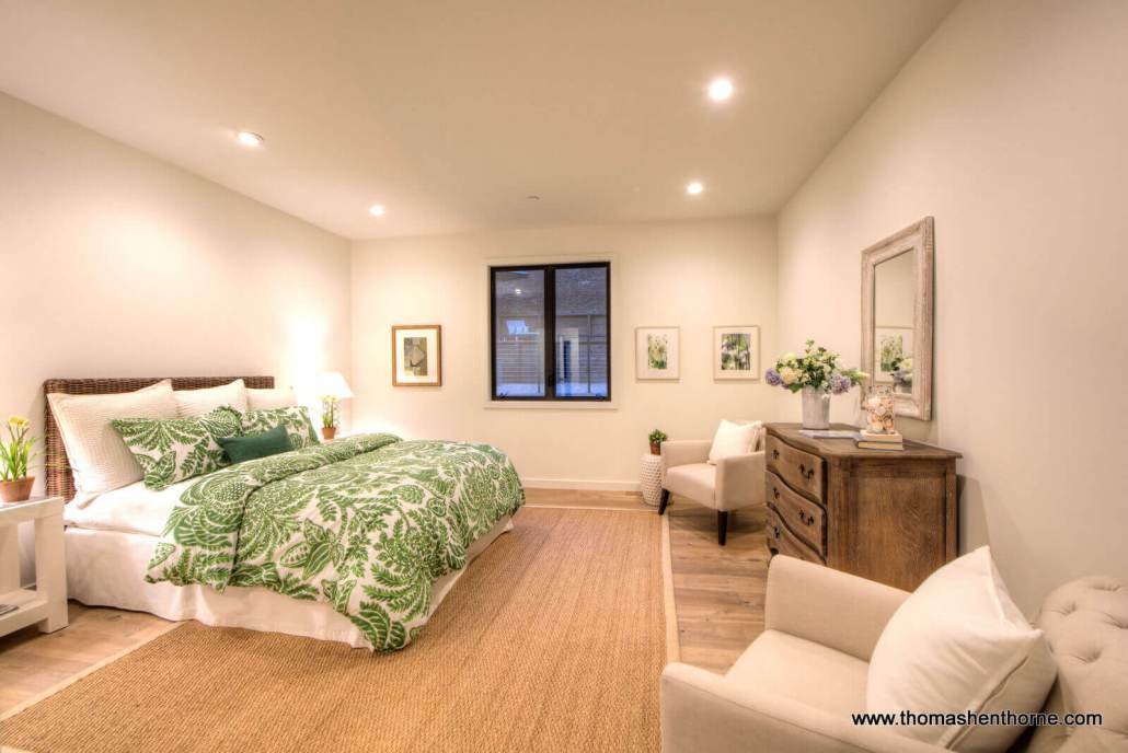 Master bedroom with green floral comforter and two chairs