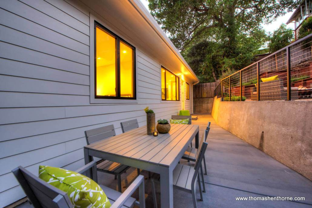 Outside dining table in back yard at dusk with green cushions