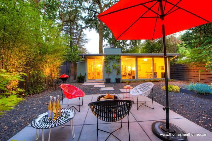 back yard with seating area and orange umbrella