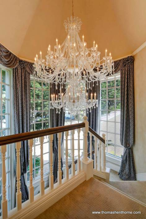 Chandelier and blue curtains in grand entry stairway at 190 Gilmartin Drive in Tiburon