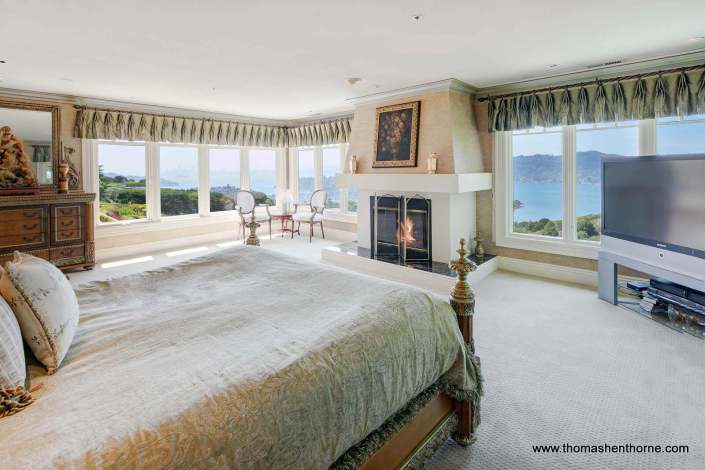 Master bedroom with view of San Francisco Bay and fireplace