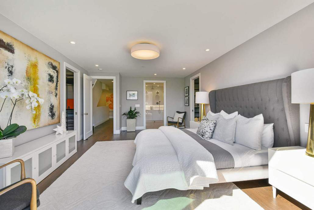 Modern bedroom with ensuite bath in distance
