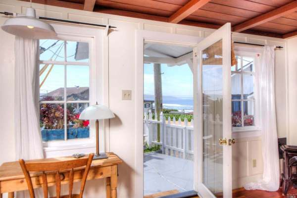 Door of cottage open looking to white picket fence and ocean in distance