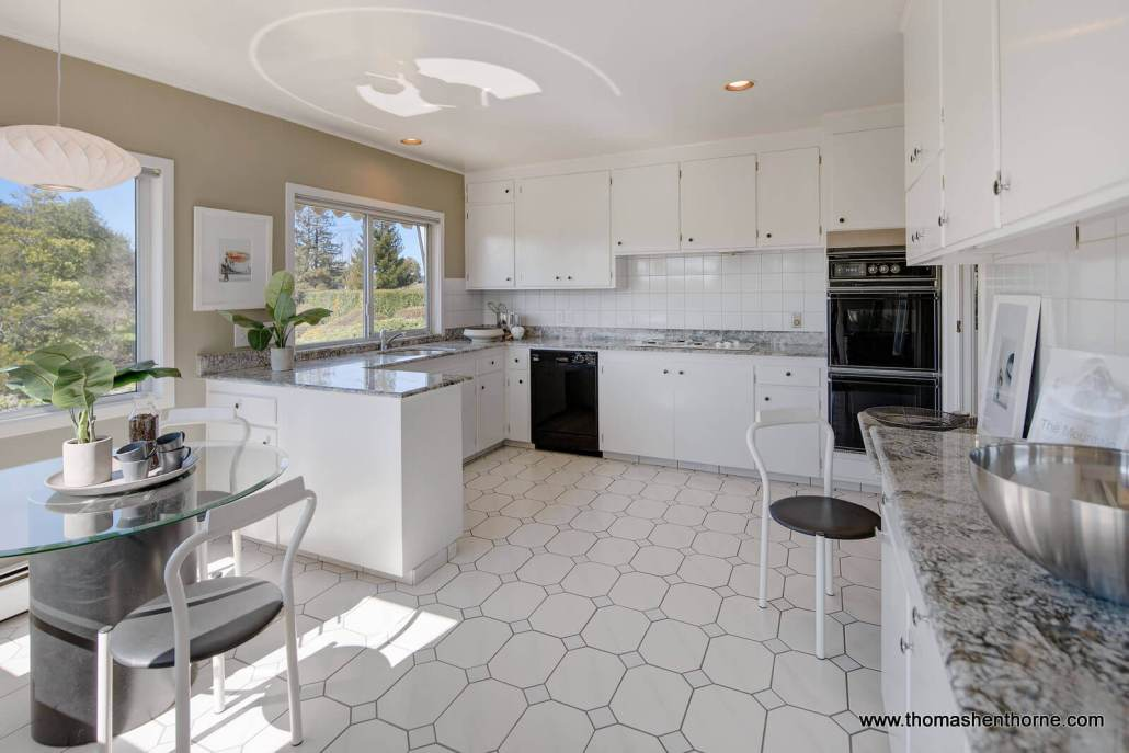 Kitchen with white tile floor and cabinets