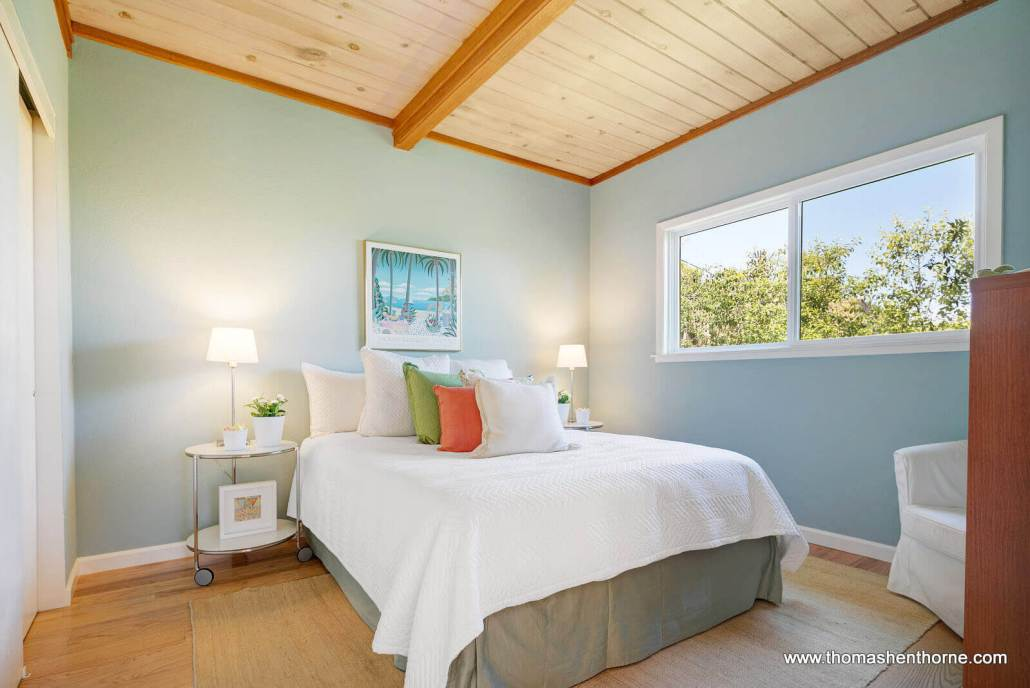 Bedroom with window and light blue walls with wood ceiling