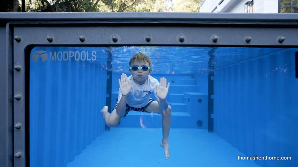 Boy swimming in Modpool with glass sides