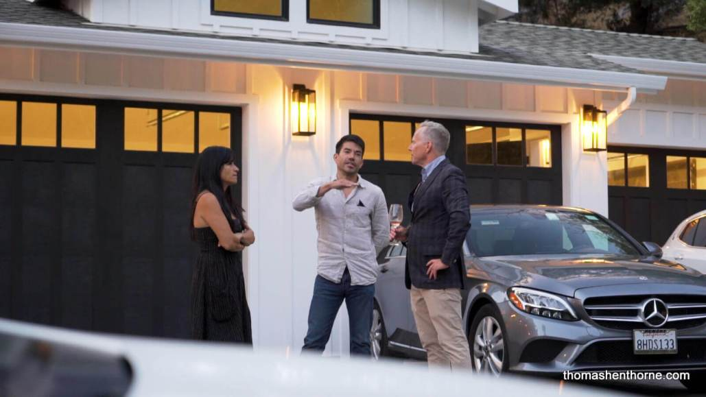 Two men and a woman talking next to a Mercedes in front of a garage
