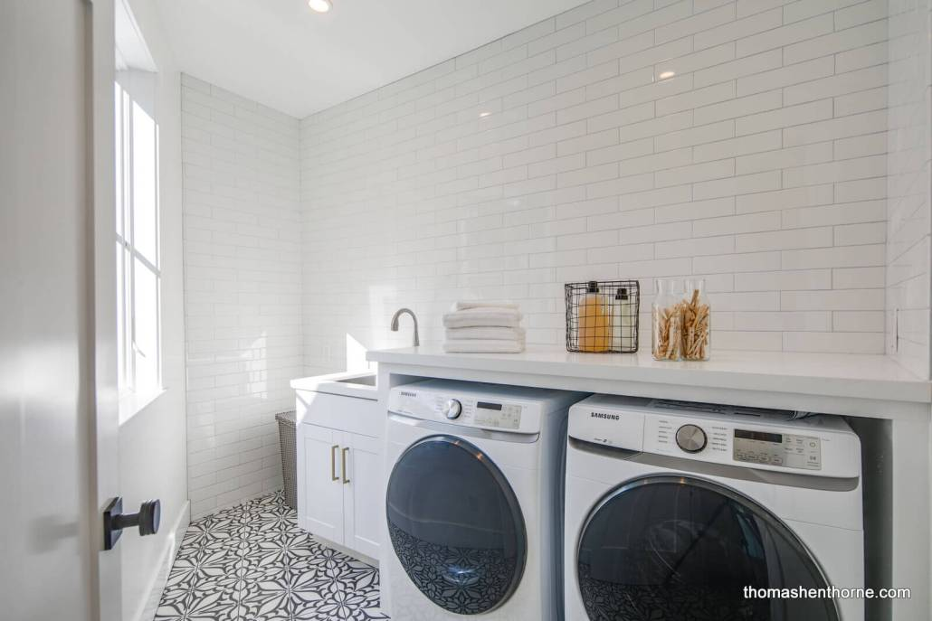Laundry room with subway tile on wall