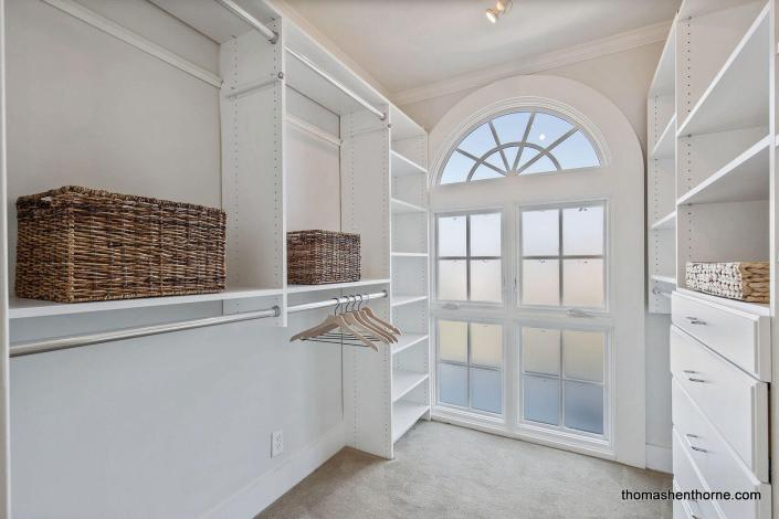 walk-in closet with arched window