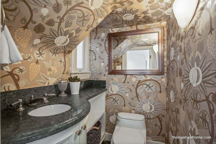 Half bathroom with bold wallpaper and marble sink