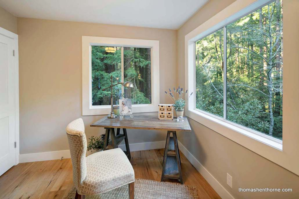 home office with windows looking out to woods