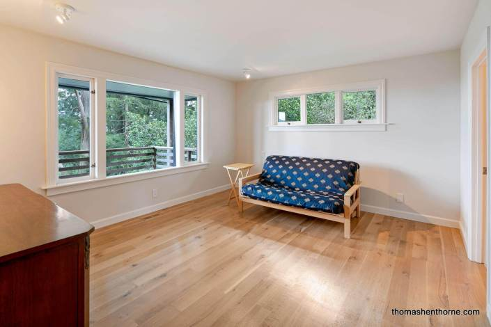 Room with wood floors and futon sofa