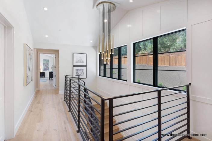 landing with metal railing and modern brass light fixture