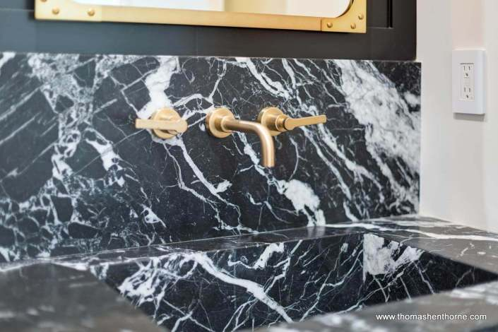 close up of marble sink with gold colored faucet and handles