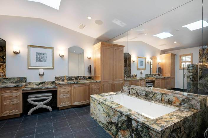 primary bathroom with soaking tub and dual sinks